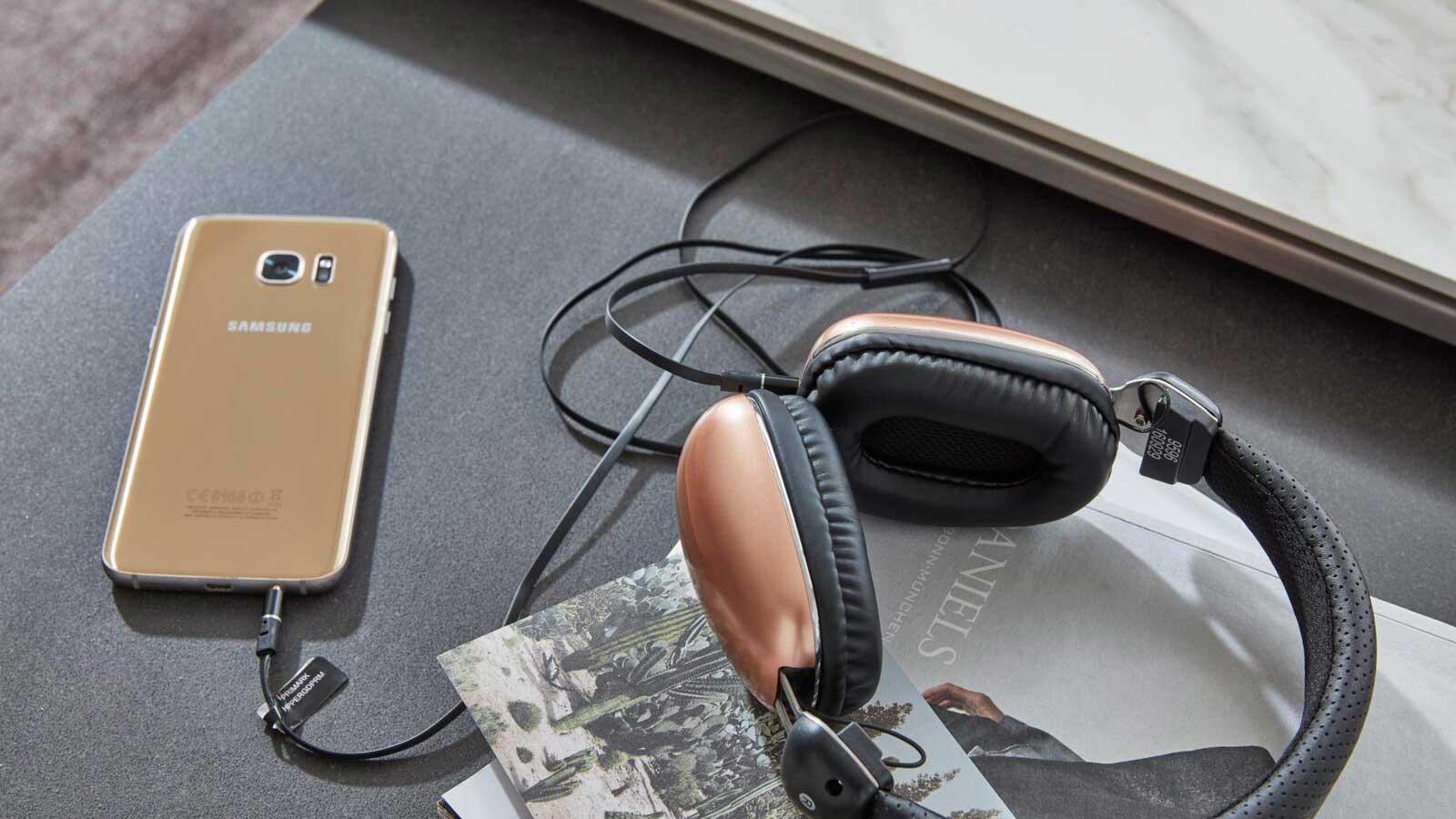 Smartphone, Kopfhörer, Notizbuch liegen bereit für Arbeit im Home Office