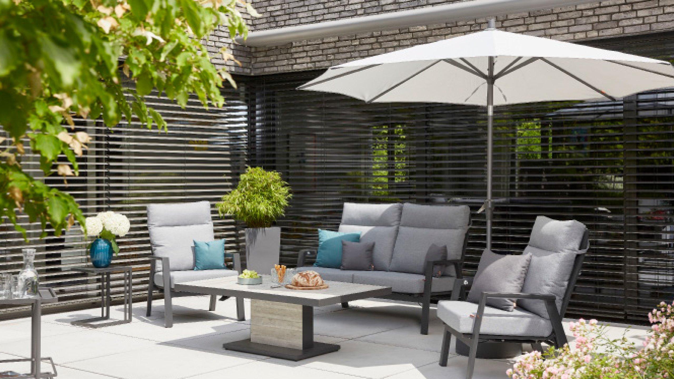 Terrasse mit Loungemöbeln und Sonnenschirm